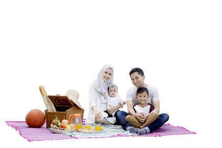 picnicking: Happy muslim family picnicking together while sitting on mat with picnic basket and foods, isolated on white background