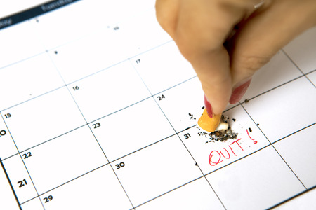 Woman hand destroying a cigarette on calendar with quit word Stock Photo