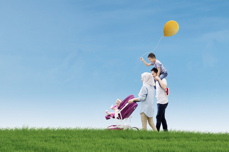 petite fille musulmane: Picture of happy parents spending time with their children while walking together in the meadow