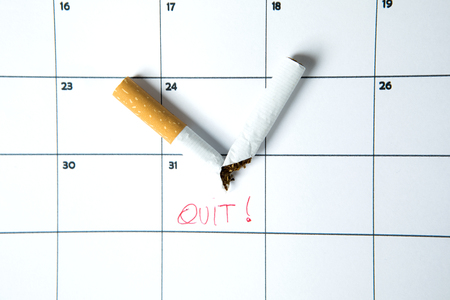 Broken cigarette above calendar date with quit word