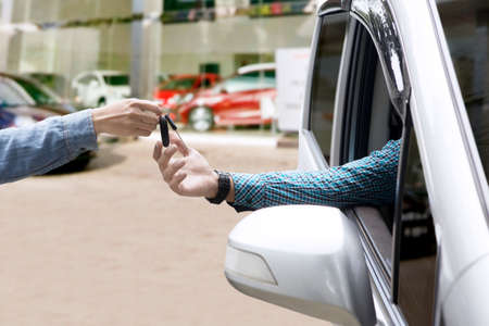 Close up of a male hand giving a car key to his client inside a new car at the showroom