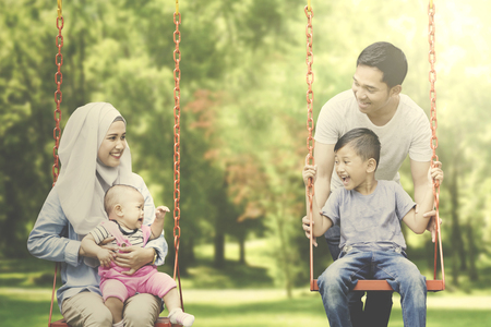 Image of cheerful Muslim family sitting in the swing while playing in the playground