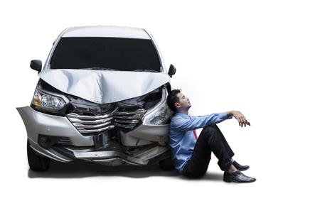 Bild eines frustrierten Geschäftsmannes, der nahe bei einem beschädigten Auto nach Unfall, lokalisiert auf weißem Hintergrund sitzt