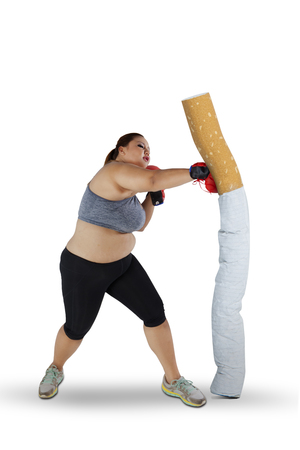 Image of blonde hair woman wearing sportswear while punching a cigarette, isolated on white background