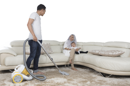 carpet clean: Young husband cleaning floor mat with vacuum cleaner while his wife smiling on the sofa, isolated on white background Stock Photo