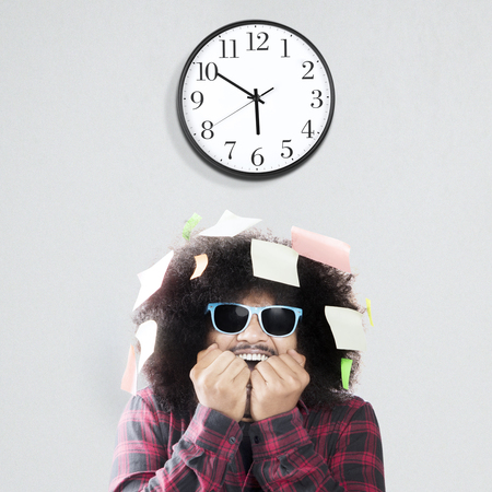 Afraid man biting nail with wall clock and sticky notes over his head, isolated on white background