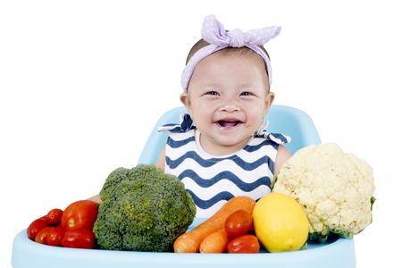 Lachende baby meisje, zittend op een kinderstoel met verse groenten, geïsoleerd op een witte achtergrond