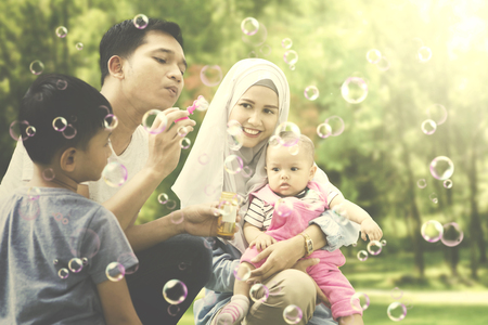 Picture of young father blowing soap bubbles while playing together with his family in the park Stock Photo