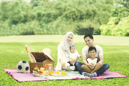Image of Muslim family smiling at the camera while picnicking in the park