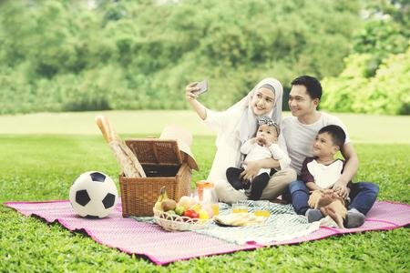 Portret van Moslimfamilie die een mobiele telefoon met behulp van om een foto samen te nemen terwijl het picknicken in het park