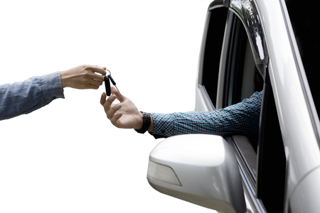 Close up of male hand giving new car key to customer, isolated on white background Stock Photo