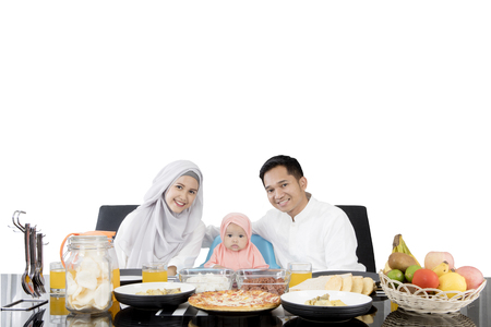 Muslim parents and cute daughter having meal at dining table while smiling at the camera, isolated on white background Stock Photo