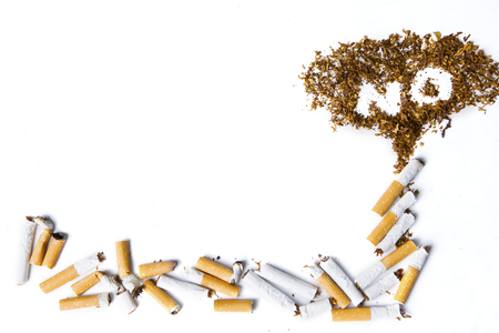 Close up No smoking sign made with broken cigarettes and tobacco, isolated on white background Stock Photo