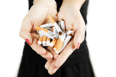 Woman showing broken cigarettes in her hand, concept of quit smoking, isolated on white background