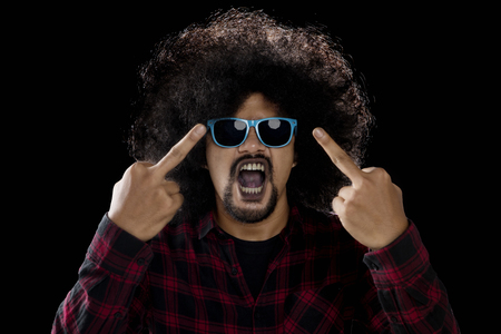 Young man showing middle finger as his angry expression while wearing sunglasses with dark background Stock Photo