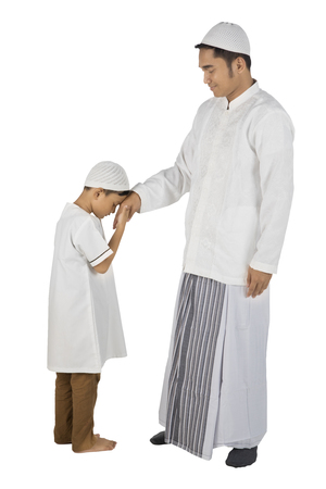 Son kissing a hand from his father as respect gesture, isolated on white background Stock Photo