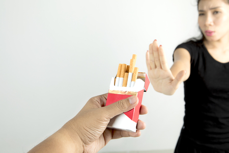offered: Woman refusing a cigarette from a pack of cigarettes offered, concept of quit smoking, isolated on white background Stock Photo