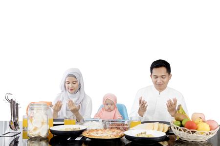 ダイニング テーブル、白い背景で隔離の前に座って食事する前に祈るイスラム教徒の家族