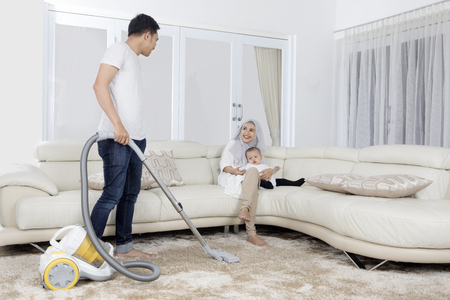 petite fille musulmane: Young man cleaning carpet with vacuum cleaner while his wife sitting on sofa in living room
