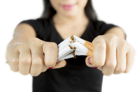 Female hand destroying cigarettes, concept of refuse bad habit, isolated on white background