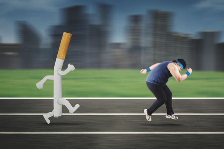 Image of obese man wearing sportswear while running away from a cigarette on the track