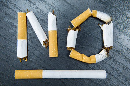 abstain: No smoking word written with broken cigarette on the table. Concept for quitting smoking Stock Photo