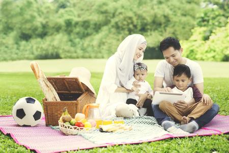 Beeld van Moslimfamilie die een digitale tablet gebruiken terwijl het picknicken in het park