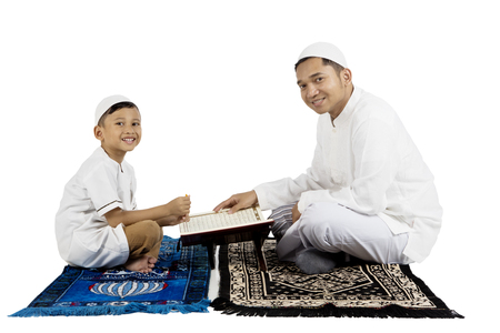 Young father and son smiling while sitting on prayer carpet with Quran, isolated on white background