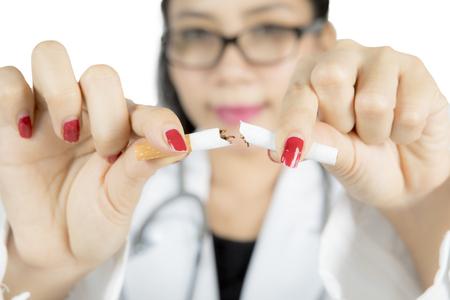 interdiction: Docteur main briser une cigarette, concept de cesser de fumer, isolé sur fond blanc Banque d'images