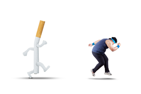 Portrait of an overweight man chased by a cigarette while running in the studio