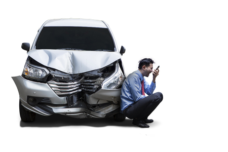 Picture of angry businessman sitting next to a damaged car while talking on his cellphone, isolated on white background