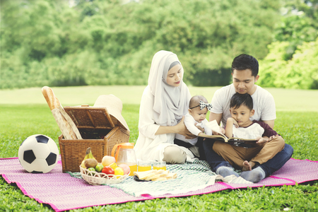 Image of young Asian family reading a book while picnicking in the park