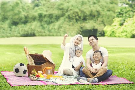 Portrait de la belle femme montrant quelque chose en pique-niquant avec sa famille dans le parc