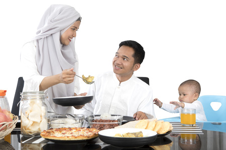 Muslim mother preparing food for family while smiling to her husband at dining table, isolated on white background