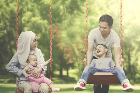 公園でのスイングを再生しながら子供たちと時間を過ごすイスラム教徒の両親のイメージ