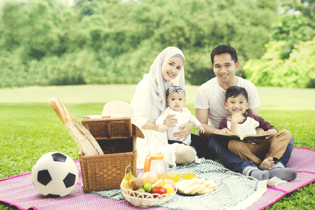Image of cheerful Muslim family looking at the camera while picnicking with a book in the park