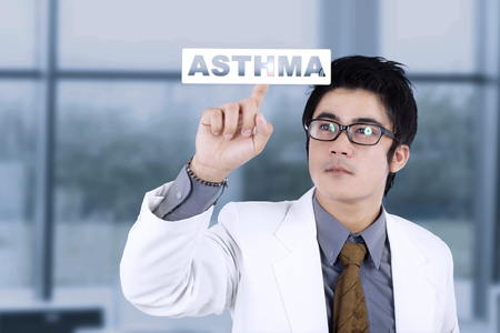Picture of male doctor touching a word of asthma on the virtual screen while standing in the hospital