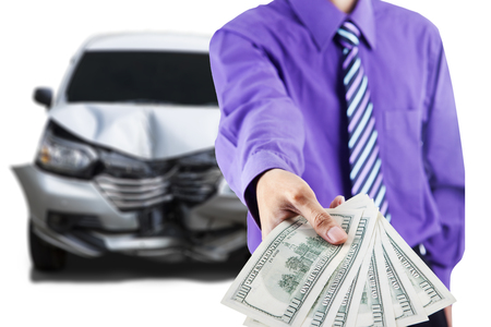 Close up of businessman hand showing dollar money in front of a damaged car after collision Stock Photo