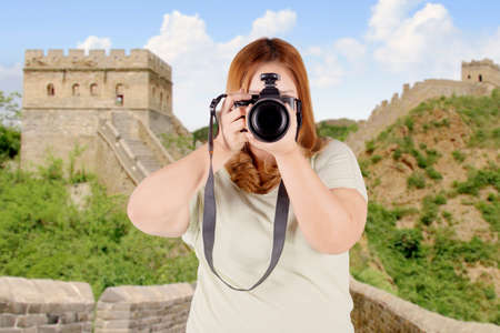 foreign bodies: Image of overweight woman using a camera to take photos while standing on the Great wall of China