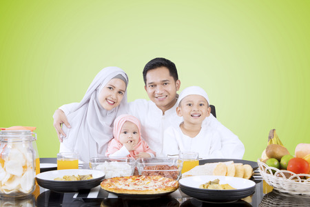 Muslim family sitting in front of dining table while smiling at the camera together