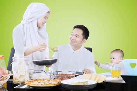 Twee jonge moslimouders en hun baby die samen op de lijst eten, schot met groene het schermachtergrond