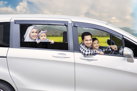 muslim: Portrait of Muslim family looking out of a car window while driving for travel on vacation Stock Photo