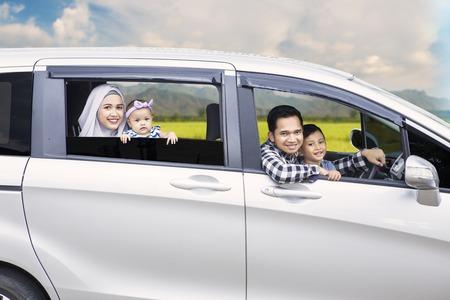 Portret van een moslimfamilie die uit een auto raakt tijdens het reizen op vakantie
