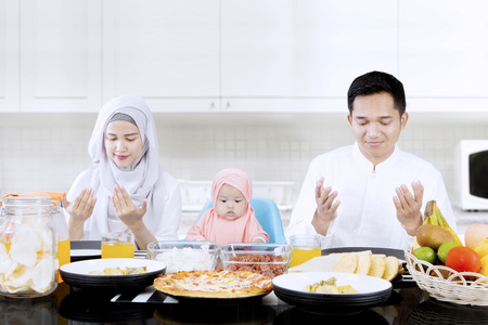Portrait of young parents and cute girl praying together in dining table while sitting in the kitchen Stock Photo