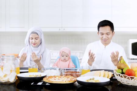 niño orando: Retrato de los padres jóvenes y linda chica orando juntos en la mesa de comedor mientras está sentado en la cocina