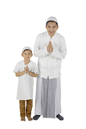 Young father and son smiling and standing with welcoming gesture, isolated on white background