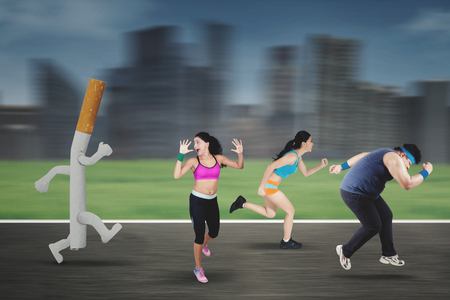 Image of runners chased by a cigarette while running in the road Stock Photo