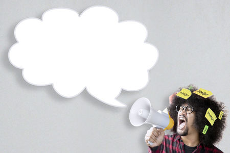 aide a la personne: Young Afro person shouting at empty cloud speech bubble through a megaphone with help texts attached on his hair