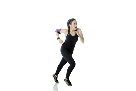 Pretty woman wearing sportswear, running and listen music with earphone, isolated on white background