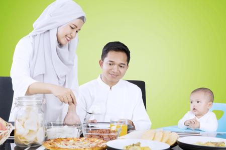 彼女は夫と子供が緑の背景で座っているダイニング テーブルの家族のための食糧を準備する若妻